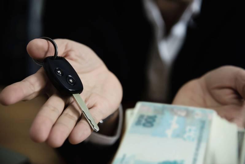 homem entregando chave e recebendo dinheiro
